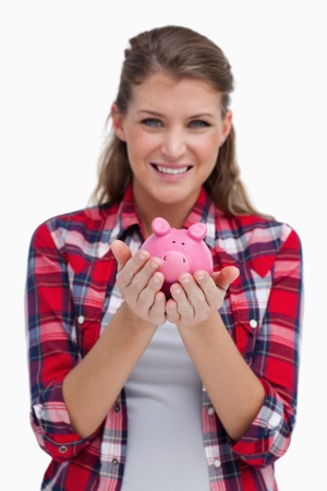 Portrait of a woman holding a piggy bank against a white background photo