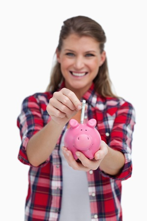 Portrait of a woman putting a note a piggy bank against a white background photo