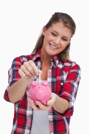 Portrait of a young woman putting a note a piggy bank against a white background photo