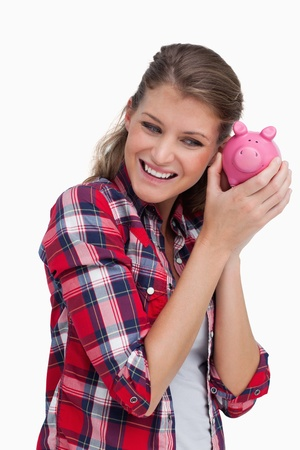 Portrait of a young woman shaking a piggy bank against a white background photo