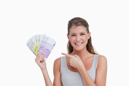 Woman pointing at bank notes against a white background photo