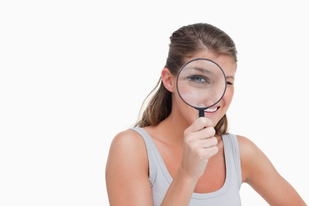 Woman looking through a magnifying glass against a white background Stock Photo - 13683878