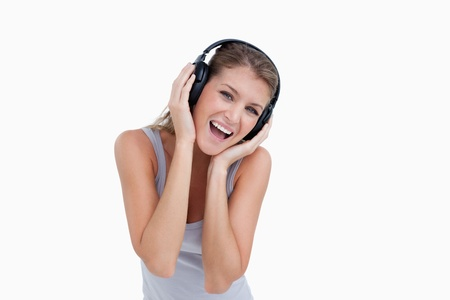 Woman singing while listening to music against a white background photo