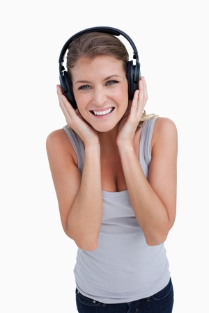 Portrait of a smiling woman listening to music against a white background photo