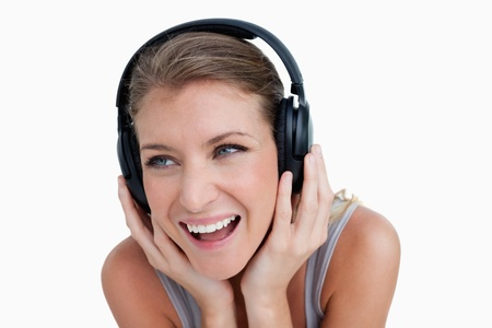 Close up of a smiling woman listening to music against a white background photo
