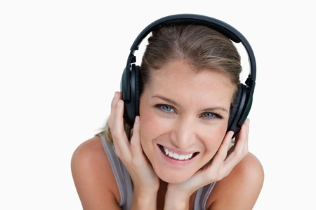 Close up of a happy woman listening to music against a white background photo