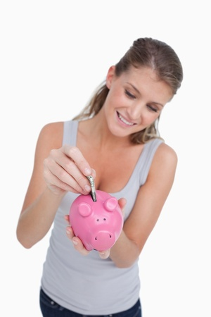Portrait of a woman putting a note in a piggy bank against a white background photo