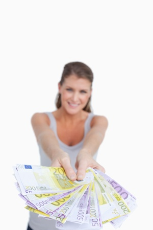 Portrait of a smiling woman showing bank notes against a white background photo