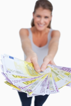 Portrait of a happy woman showing bank notes against a white background photo