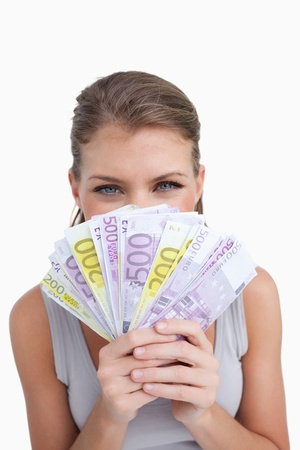 Portrait of a happy woman smelling bank notes against a white background photo