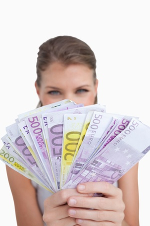 Portrait of a cute woman showing bank notes against a white background photo