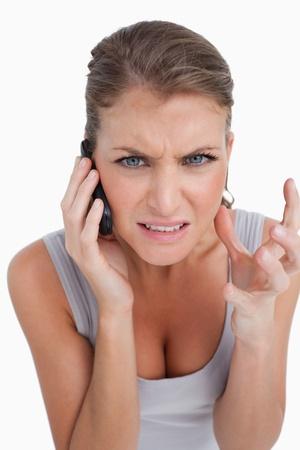 Retrato de una mujer enojada hacer una llamada telef�nica sobre un fondo blanco photo