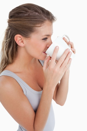 Portrait of a woman drinking a cup of coffee against a white background photo