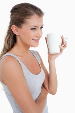 Portrait of a woman holding a cup of tea against a white background photo