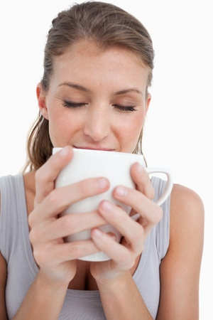 Portrait of a smiling woman holding a cup of coffee against a white background photo