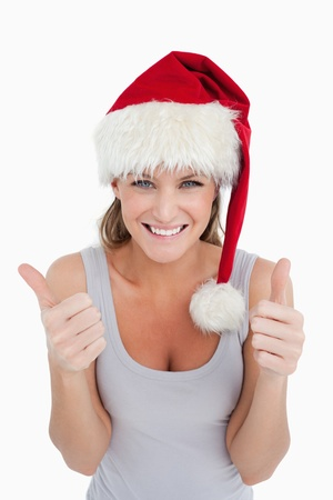 Portrait of a woman with the thumbs up and a Christmas hat against a white background photo