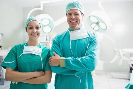 enfermeros: Cirujanos sonrientes mirando a la c�mara en un quir�fano Foto de archivo