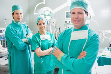 Smiling surgeons looking at camera with crossed arms in an operating theatre photo