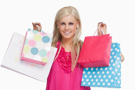 Smiling blonde showing shopping bags against white background Stock Photo - 15551639