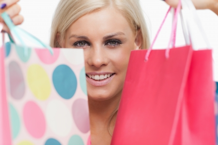 Smiling blonde showing her shopping bags against white background Stock Photo - 15551495