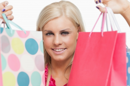 Pretty blonde holding shopping bags against white background Stock Photo - 15551512