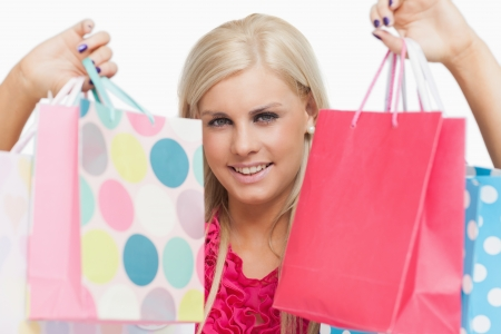 Beautiful blonde showing shopping bags against white background Stock Photo - 15551510