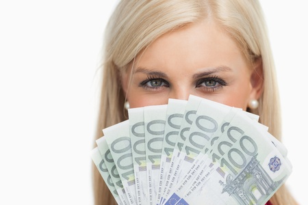 Pretty blonde holding 100 euros banknotes against white background photo