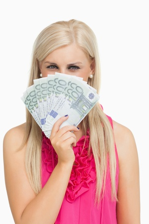 argent: Blonde in pink holding 100 euros banknotes against white background Stock Photo