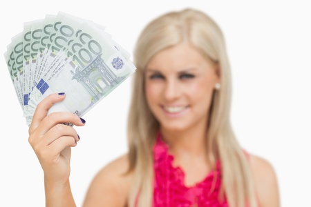 argent: Beautiful blonde showing 100 euros banknotes against white background