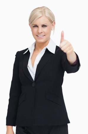 Smiling blond businesswoman thumb-up against white background photo
