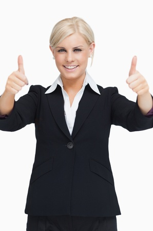 Smiling blond businesswoman thumbs-up against white background photo