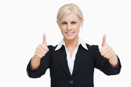 thumbsup: Smiling blonde businesswoman thumbs-up against white background