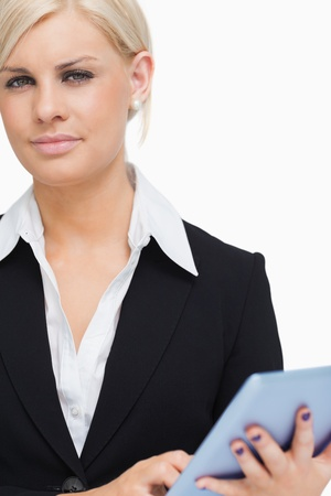 Green eyed businesswoman holding a tactile tablet against white background photo