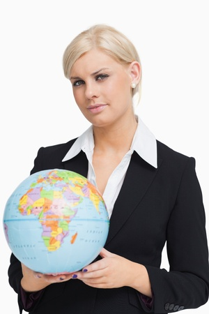 Serious businesswoman holding a globe against white background photo