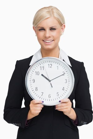 Serious blonde in suit holding a clock against white background photo