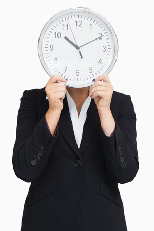 Businesswoman in suit holding a clock against white background photo