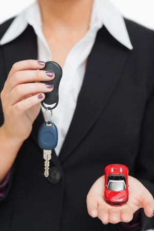 Woman holding key and small car in her palm against white background Stock Photo - 15551501