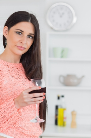 Brunette holding a glass of wine in a kitchen photo