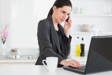 brown hair: Woman calling while using a laptop in kitchen Stock Photo