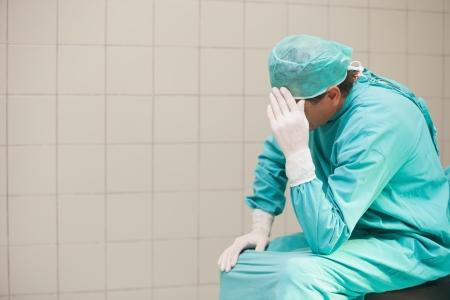 desolaci�n: Cirujano pensativo sentado en una sala de operaciones con la mano en la cabeza