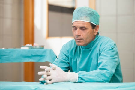 solicitous: Thoughtful surgeon sitting in a operating room in a hospital