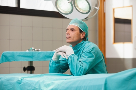 quietness: Reflective surgeon sitting in a operating theater in a hospital Stock Photo