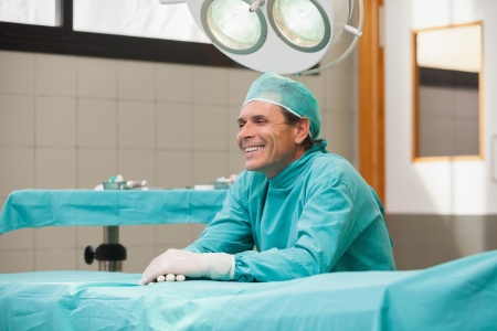Happy surgeon sitting in a operating theater in a hospital feeling relieved photo