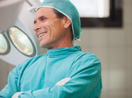 Surgeon smiling with arms crossed in operating theatre in hospital photo