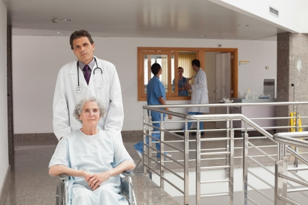Old weak woman sitting on the wheelchair being pushed by doctor Stock Photo - 15591752