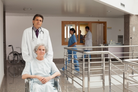 Old woman sitting in a wheelchair while the doctor is pushing in hospital corridor photo