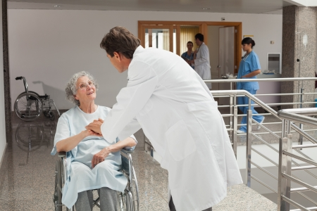 Old woman sitting on a wheelchair in a hospital while talking with the doctor photo