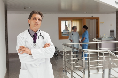 Doctor standing in the hallway while crossing his arms and looking serious photo