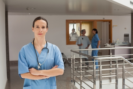 Doctor standing in the hallway of a hospital while crossing her arms photo