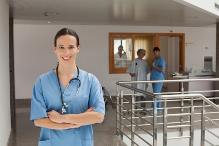 Smiling doctor standing in the hallway of a hospital while crossing her arms photo